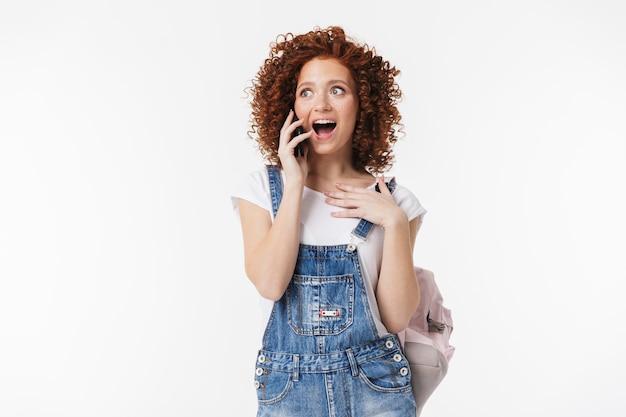 Obraz piękny szok kręcone szczęśliwe rude dziewczyny pozowanie na białym tle nad białą ścianą rozmawia przez telefon komórkowy.
