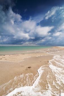 Obraz plaży i dramatyczne niebo.