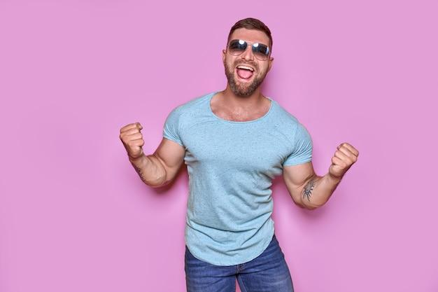 Obraz podekscytowanego brodatego mężczyzny w okularach przeciwsłonecznych gest zwycięzcy na białym tle różowym tle