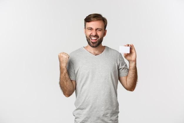 Obraz podekscytowanego brodatego mężczyzny w szarym t-shircie, pokazującego kartę kredytową i wykonującego pompkę pięścią, mówiącego tak