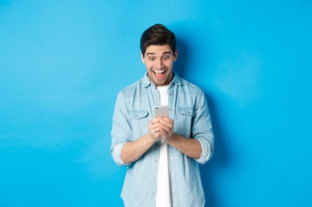 Obraz podekscytowanego mężczyzny uśmiechającego się, patrzącego na telefon komórkowy, robiącego zakupy online na smartfonie, stojącego na niebieskim tle