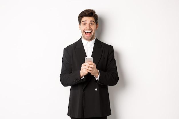 Obraz podekscytowanego przystojnego faceta otrzymującego ofertę promocyjną na telefon komórkowy