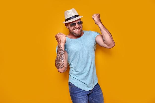 Obraz podekscytowanego, wytatuowanego mężczyzny w okularach przeciwsłonecznych i kapeluszu, który wykonuje gest zwycięzcy na białym tle żółtej ba...