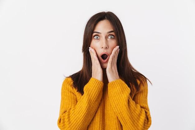 Obraz podekscytowanej brunetki dorosłej kobiety noszącej sweter wyrażający zaskoczenie i zdziwienie z otwartymi ustami na białym tle