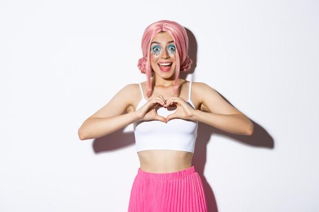 Obraz podekscytowanej uśmiechniętej dziewczyny jak coś, pokazujący gest serca i wyglądający na zaskoczonego
