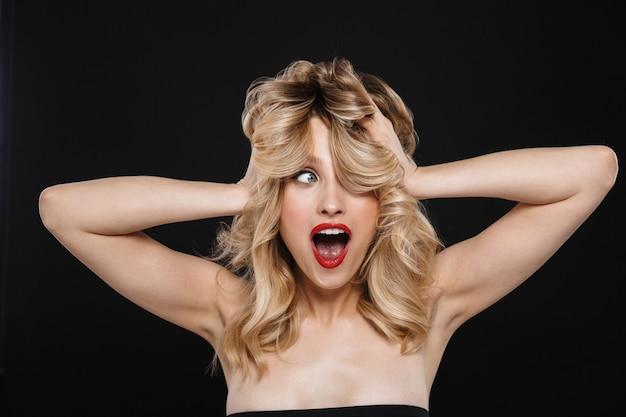 Obraz podekscytowany młoda piękna kobieta emocjonalna z jasny makijaż czerwone usta pozowanie na białym tle.