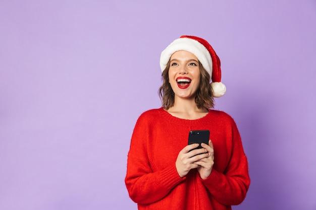 Obraz podekscytowany zszokowany młoda kobieta ubrana w kapelusz boże narodzenie na białym tle nad fioletową ścianą za pomocą telefonu komórkowego.
