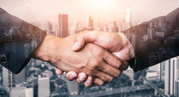 Obraz podwójnej ekspozycji uścisk dłoni ludzi biznesu na biurowcu miasta pokazując partnerstwo