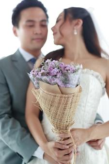 Obraz portretu. pan młody i panna młoda stoją, uśmiechają się i przytulają w tle sukni panny młodej. kobieta trzyma fioletowy bukiet reprezentuje miłość do człowieka. koncepcja ślubu najlepszy dzień.