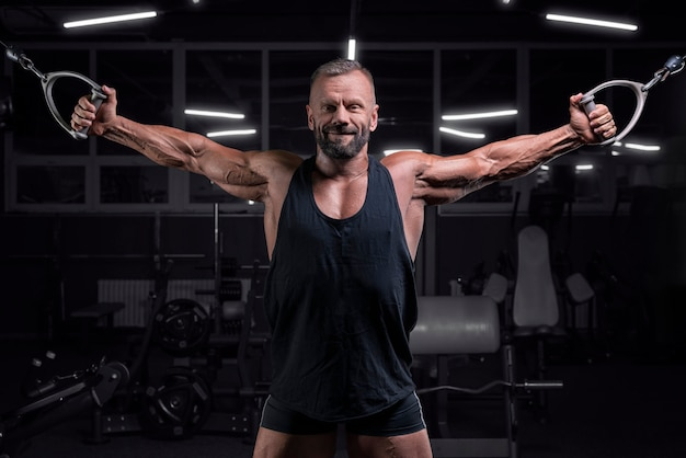 Obraz potężnego sportowca ćwiczącego w crossoverze na siłowni. koncepcja fitness i kulturystyki. różne środki przekazu