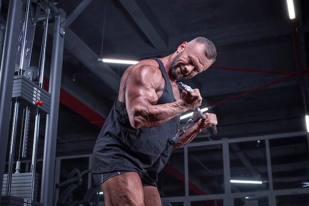 Obraz potężnego sportowca ćwiczącego w crossoverze na siłowni. pompowanie bicepsów. koncepcja fitness i kulturystyki. różne środki przekazu