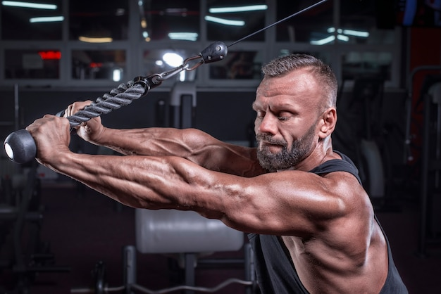 Obraz potężnego sportowca ćwiczącego w crossoverze na siłowni. pompowanie tricepsa. koncepcja fitness i kulturystyki. różne środki przekazu