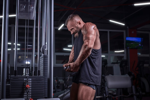 Obraz potężnego sportowca podnoszącego ciężary na siłowni. pompowanie ramion. koncepcja fitness i kulturystyki. różne środki przekazu