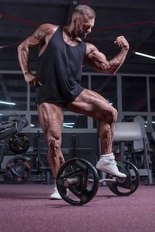 Obraz potężnego sportowca pozującego na siłowni. koncepcja fitness i kulturystyki. różne środki przekazu