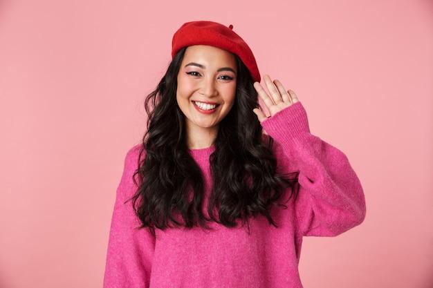 Obraz pozytywnej pięknej azjatyckiej dziewczyny z długimi ciemnymi włosami, noszącej beret machający ręką