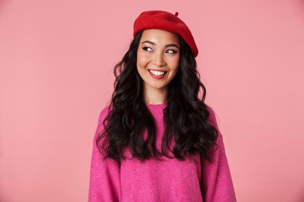 Obraz pozytywnej pięknej azjatyckiej dziewczyny z długimi ciemnymi włosami w berecie z uśmiechem