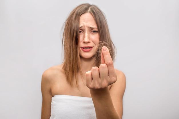Obraz problemu z włosami, jaki ma młoda kobieta. między palcami są jej włosy. ona jest przerażona to dla niej katastrofa.