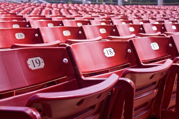 Obraz przedstawiający czerwone składane puste siedzenia stadionowe z metalowymi tabliczkami z numerami siedzeń