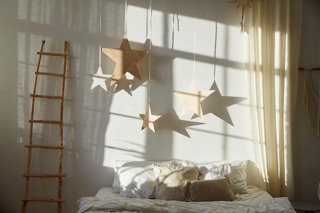 Obraz przedstawiający nowoczesną sypialnię z łóżkiem i dekoracją w kształcie gwiazdek