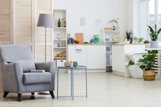 Obraz przedstawiający nowoczesny fotel stojący w salonie z białą kuchnią