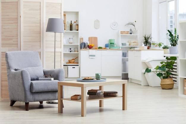 Obraz przedstawiający nowoczesny salon z fotelem w domu z nowoczesną kuchnią