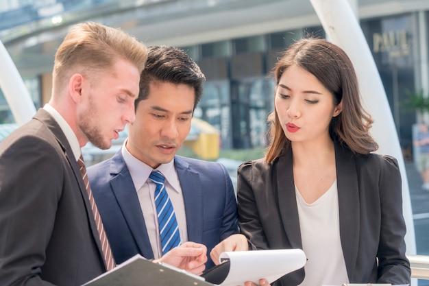 Obraz przedstawiający partnerów biznesowych omawiających pracę i pomysły z dokumentami podczas spotkania na świeżym powietrzu dla pieszych
