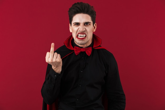 Obraz przerażającego wampira z krwią i kłami w czarnym kostiumie na halloween pokazującym środkowy palec