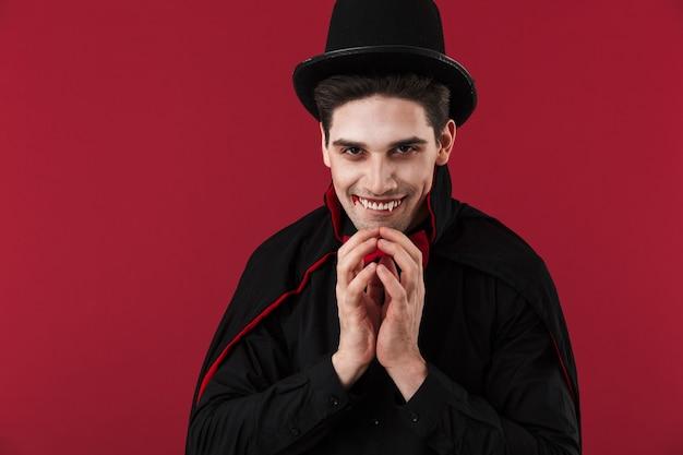 Obraz przerażającego wampira z krwią i kłami w czarnym kostiumie na halloween