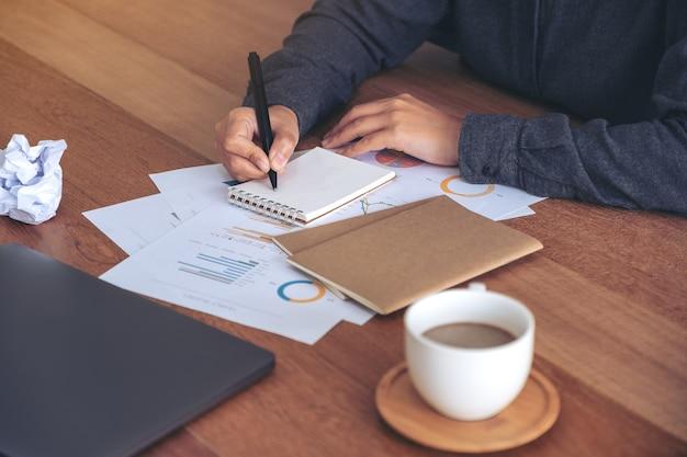 Obraz przeznaczone do walki radioelektronicznej z businesswoman pracy i zapisywania na białym pustym notatniku z przykręcony papier i laptop na stole w biurze