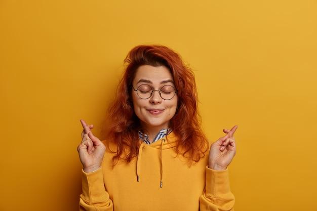 Obraz przyjemnie wyglądającej, pełnej nadziei rudej kobiety trzymającej kciuki, życzy powodzenia przed egzaminem lub pójściem na rozmowę kwalifikacyjną, zamyka oczy