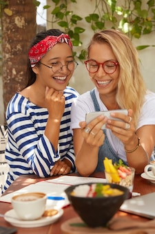 Obraz przyjemnie wyglądających, radosnych, wieloetnicznych kobiet oglądających komedię na telefonie komórkowym