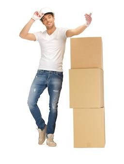 Obraz przystojnego budowniczego z dużymi pudełkami.