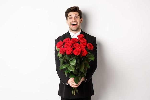 Obraz przystojnego chłopaka w czarnym garniturze, trzymającego bukiet czerwonych róż i uśmiechającego się, będącego na randce, stojącego na białym tle