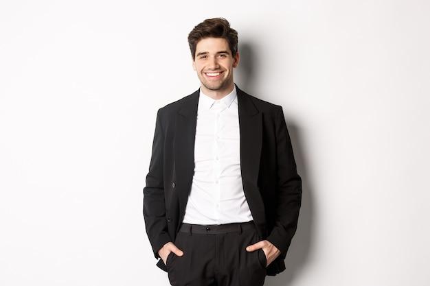Obraz przystojnego mężczyzny rasy kaukaskiej w kostiumie imprezowym, uśmiechniętego z zadowoleniem, uczestniczącego w formalnym wydarzeniu, stojącego na białym tle