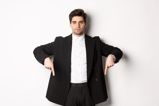 Obraz przystojnego mężczyzny ubranego na uroczystą imprezę, w garniturze i wskazującego palcami w dół, pokazującego reklamę lub wydającego ogłoszenie, stojącego na białym tle