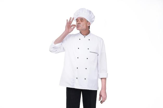 Obraz przystojnego starszego szefa kuchni w pomieszczeniu na białym tle nad białą ścianą