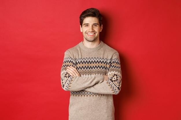 Obraz przystojnego szczęśliwego faceta w świątecznym swetrze, uśmiechającego się i patrzącego w kamerę, świętującego święta bożego narodzenia, stojącego na czerwonym tle