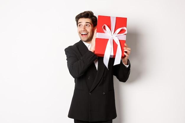 Obraz przystojny marzycielski facet w czarnym garniturze, potrząsając pudełkiem z prezentem, aby się zastanawiać, co jest w środku, stojąc na białym tle szczęśliwy.
