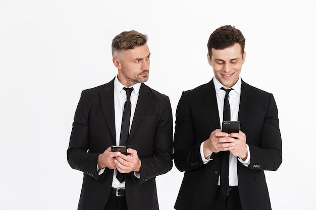 Obraz przystojnych dwóch biznesmenów rasy kaukaskiej w garniturach biurowych, trzymających i piszących na telefonach komórkowych na białym tle