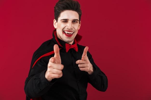 Obraz radosnego wampira z krwią i kłami w czarnym kostiumie na halloween wskazującym palcem z przodu