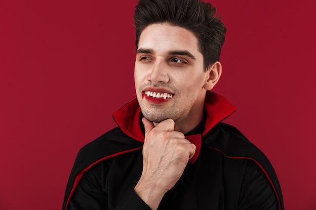 Obraz radosnego wampira z krwią i kłami w czarnym kostiumie na halloween