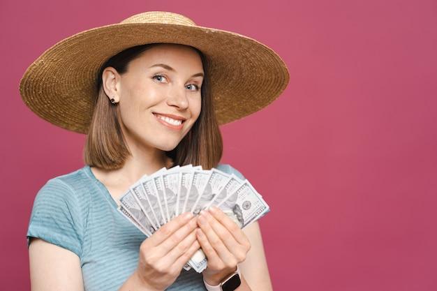 Obraz radosnej młodej damy w niebieskiej letniej koszulce i dużym kapeluszu szczęśliwie trzyma pieniądze na różowej ścianie