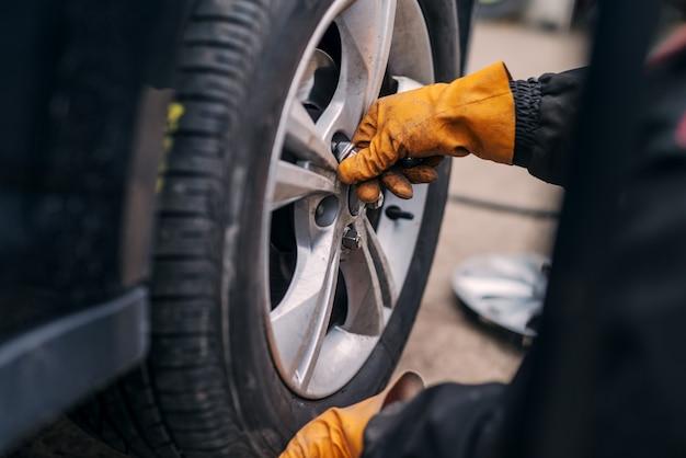 Obraz rąk mechanika samochodowego stawiając oponę samochodową na cr w warsztacie.