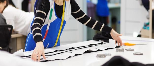 Obraz rąk projektanta pracujących w warsztacie. kobieta w trakcie tworzenia nowej kolekcji ubrań.