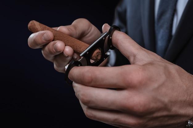 Obraz rąk trzymających gilotynę i cygaro. koncepcja klubów cygarowych. różne środki przekazu