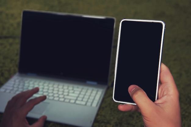Obraz ręki mężczyzny trzymającej telefon komórkowy z czarnym ekranem i rozmycie srebrny laptop na zielonej miękkiej powierzchni jako tło. korzystanie z gadżetów w domu. człowiek przerywa pracę laptopa, aby odebrać telefon.