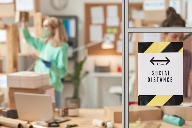 Obraz reklamy przedstawiającej dystans społeczny wiszący na szklanej ścianie w biurze