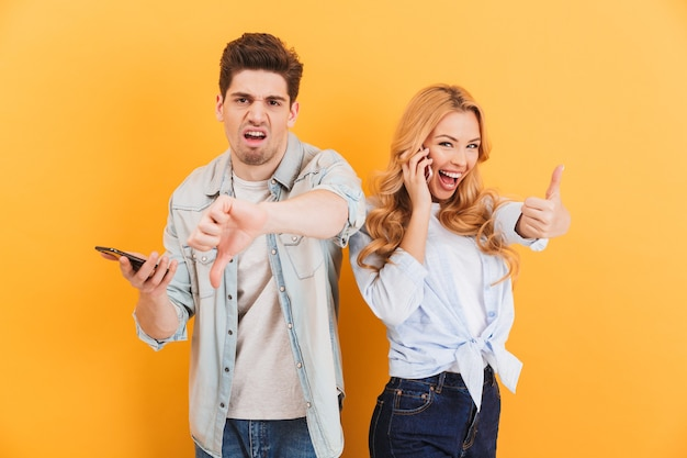 Obraz rozczarowanego mężczyzny za pomocą smartfona i pokazujący kciuk w dół, podczas gdy szczęśliwa kobieta gestykuluje palec po rozmowie telefonicznej