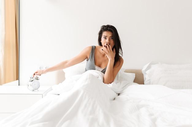 Obraz rozczarowanej kobiety 20s wyłączającej dzwonek budzika na szafce nocnej, budzącej się i spóźnionej