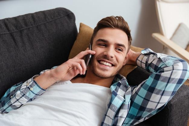 Obraz roześmianego włosia mężczyzny ubranego w koszulę w klatce wydruku leży na kanapie w domu i rozmawia przez telefon.